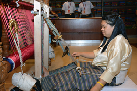 A Bhutanese artisan shows visitors how tigma fabric is woven